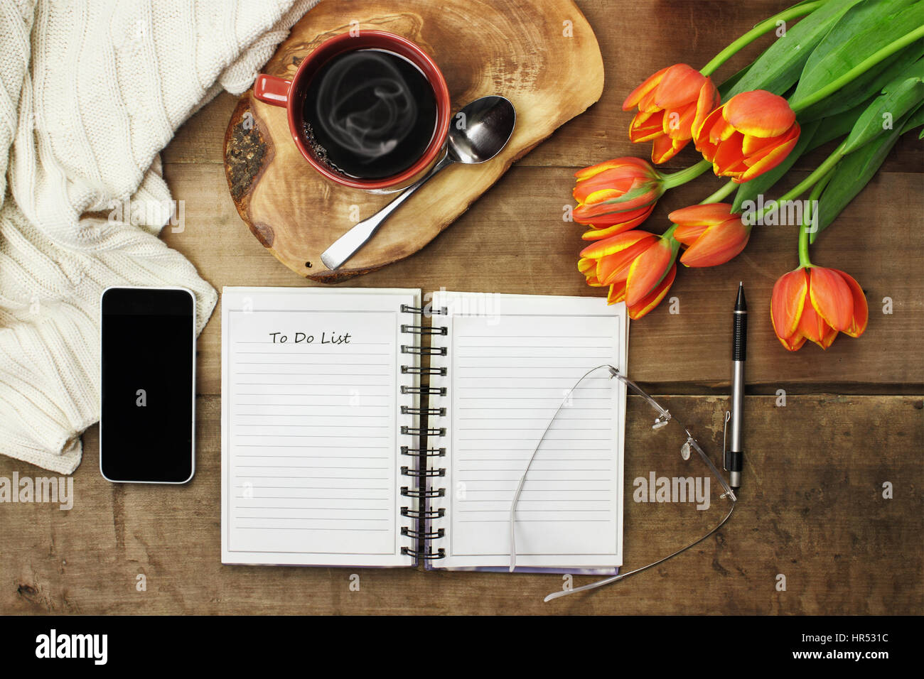 Overhead of an open book, cell phone, coffee and flowers over a wood table top ready to plan an agenda. Flat lay - Stock Image