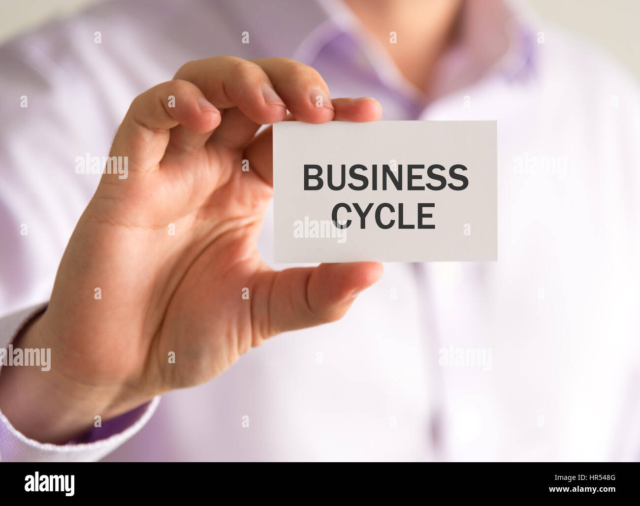 Closeup on businessman holding a card with BUSINESS CYCLE message, business concept image with soft focus background - Stock Image