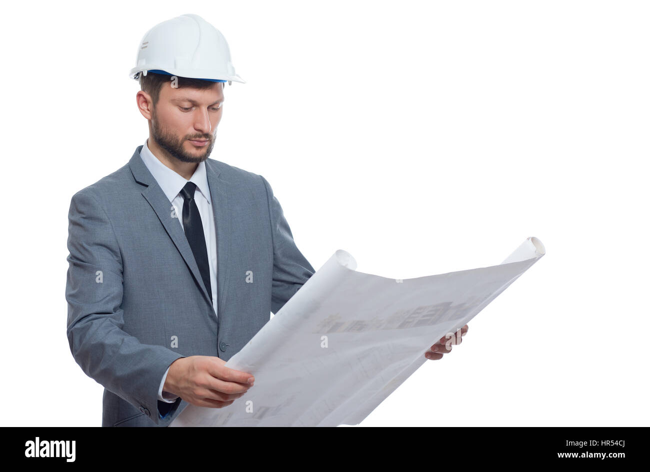 Diligent professional. Handsome mature bearded male architect wearing hardhat looking serious while examining blueprints - Stock Image