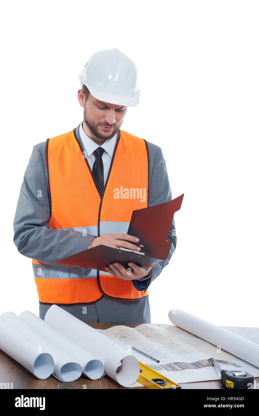 Constructionist businessman. Mature male constructionist wearing safetu vest and a hardhat making notes on his clipboard - Stock Image