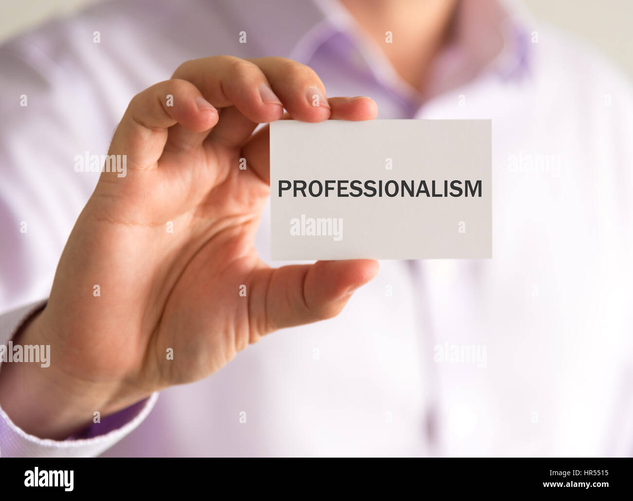 Closeup on businessman holding a card with PROFESSIONALISM message, business concept image with soft focus background - Stock Image
