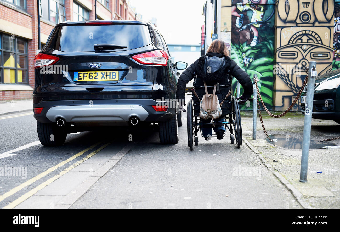 Wheelchair user struggles to pass by badly parked car on pavement and double yellow lines in Brighton UK - Stock Image