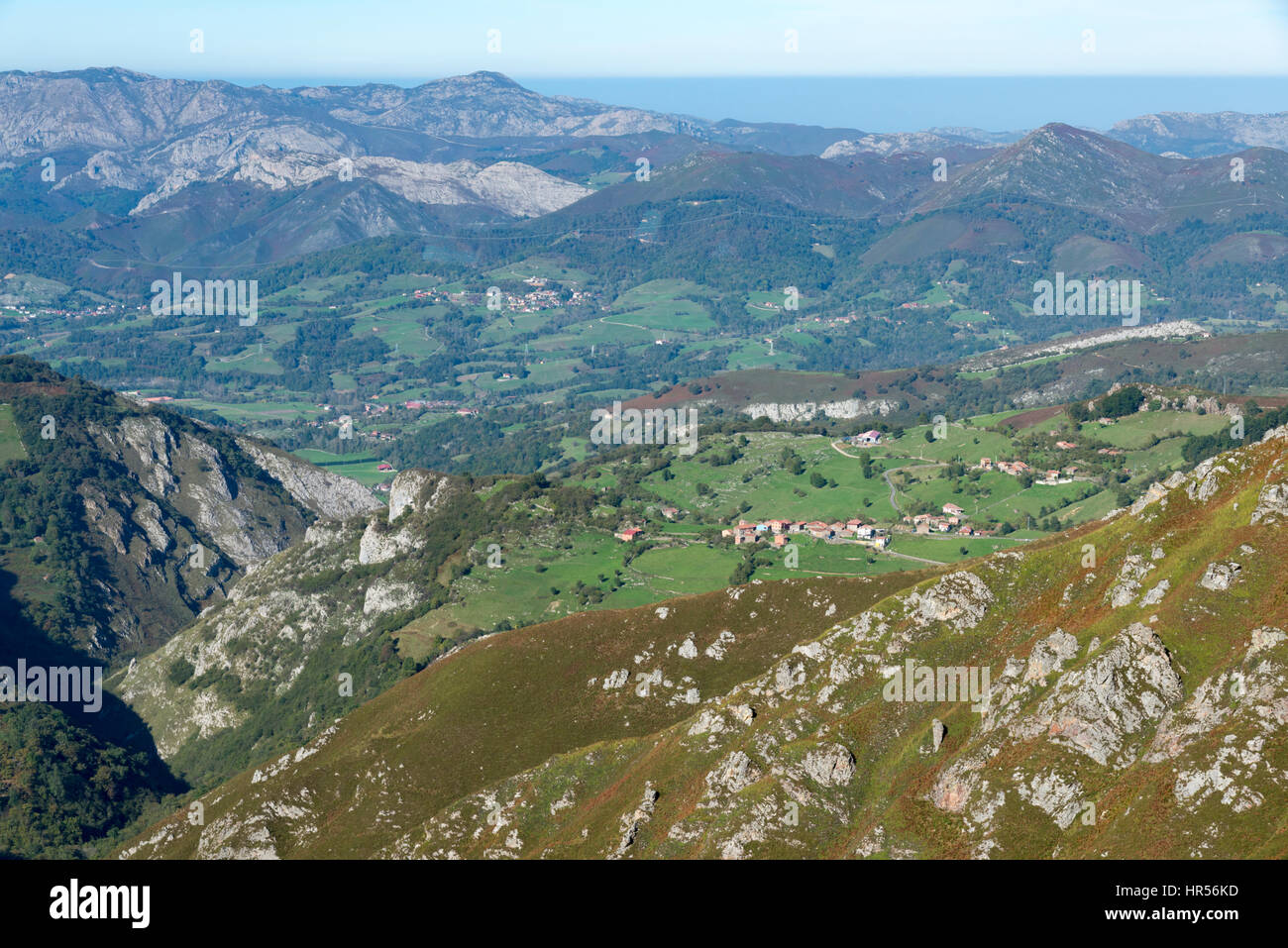 A landscape view of limestone hills and mountains with houses, villages and hill farms in the Picos de Europa Asturias - Stock Image
