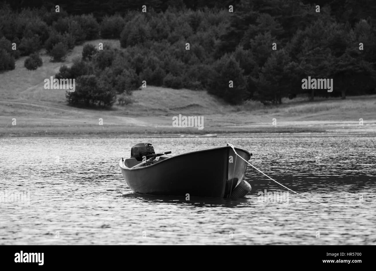 high mountain bulgarian lake with fishing boat in foreground, black and white boat background - Stock Image
