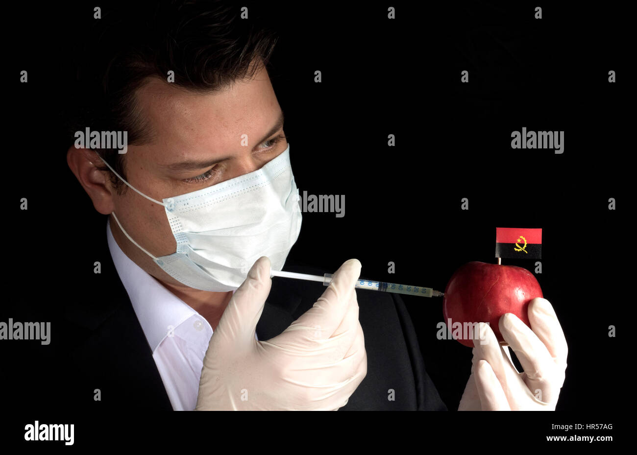 Young businessman injecting chemicals into an apple with Angolan flag on black background Stock Photo