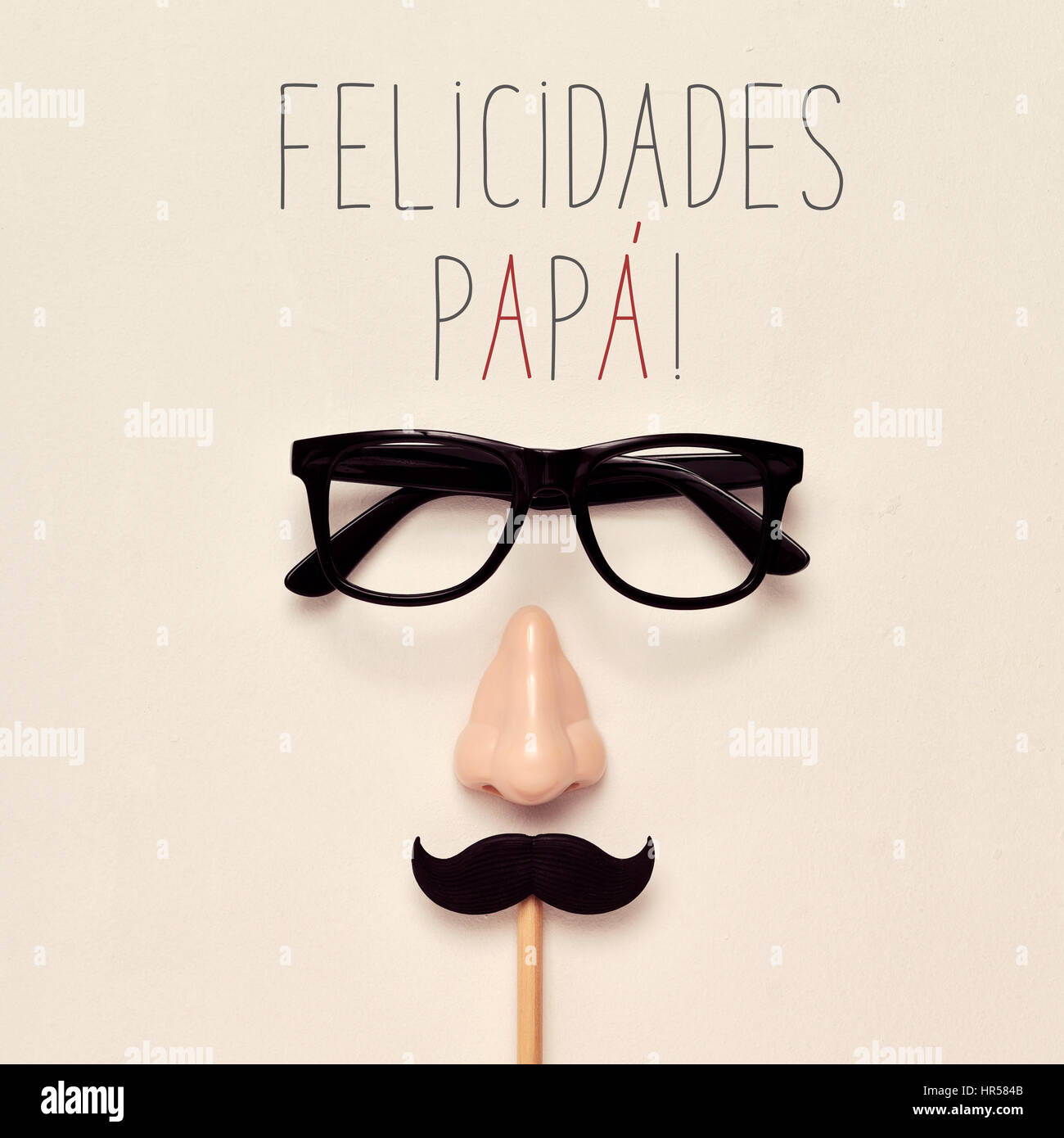 the text felicidades papa, congratulations daddy in spanish, a pair of black plastic-rimmed eyeglasses, a nose and - Stock Image