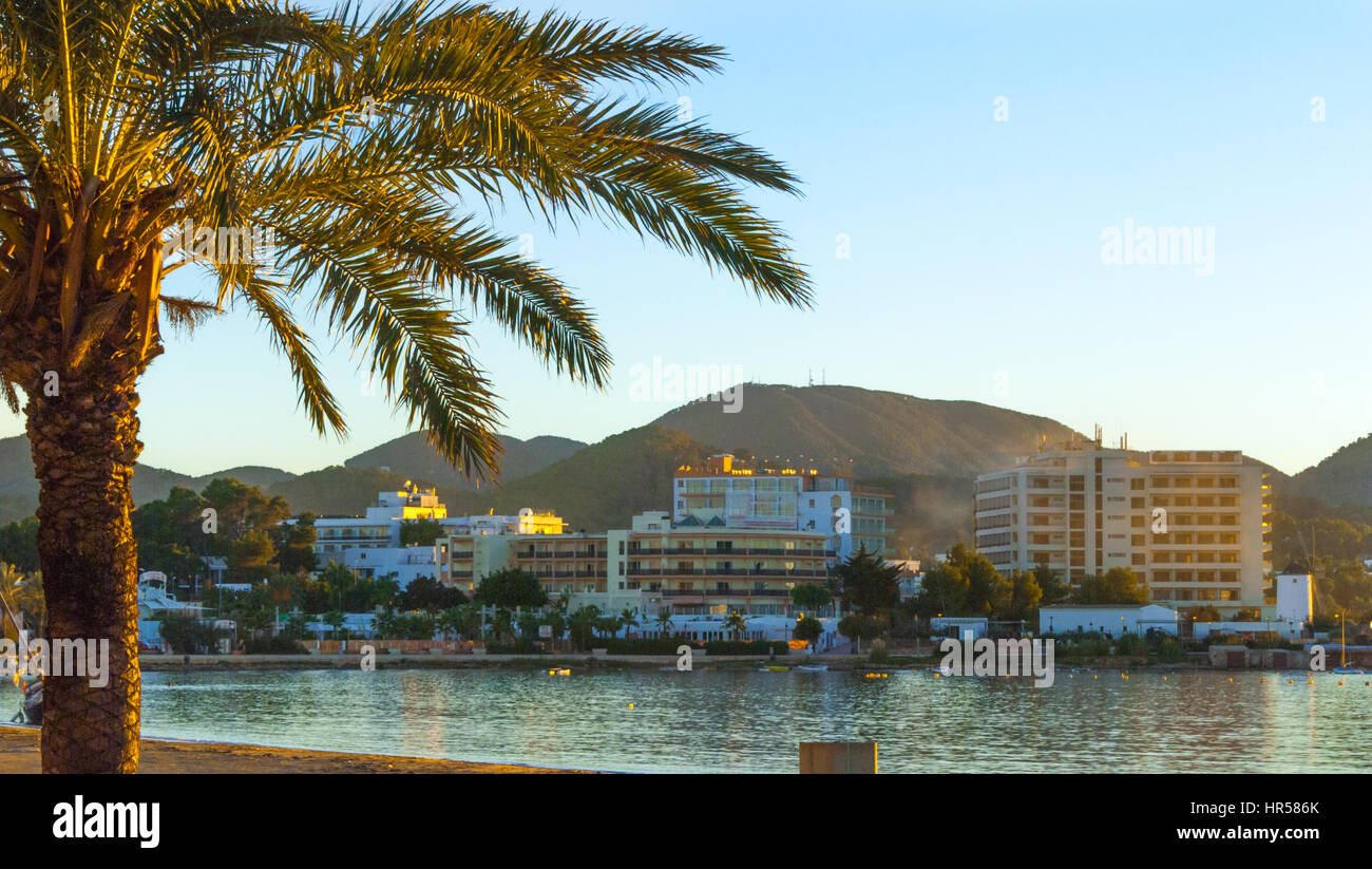 Late afternoon sun falls on the bay.  St Antoni de Portmany, Ibiza, Spain.  Hotels along the shoreline in golden - Stock Image