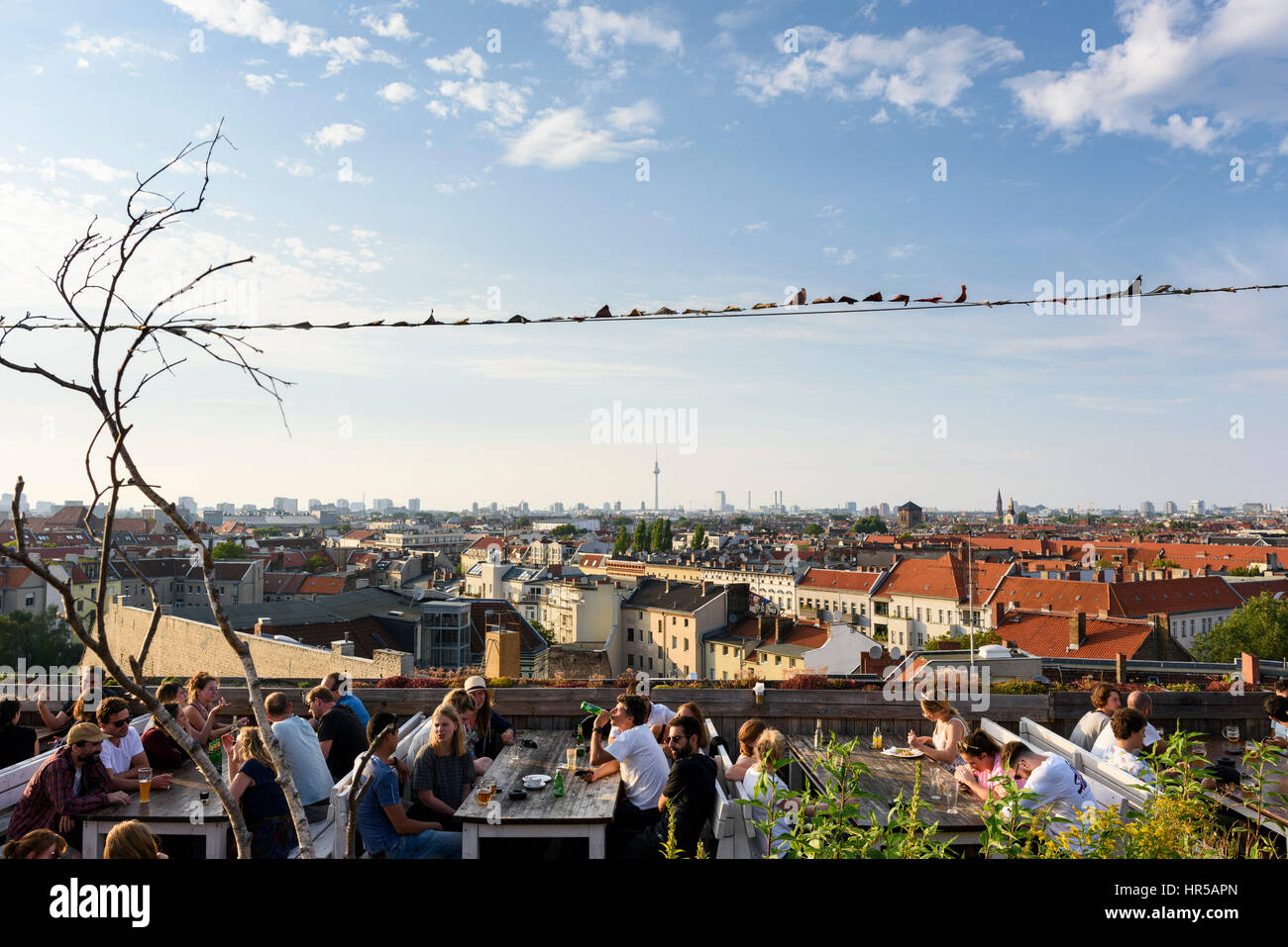 Berlin. Germany. People enjoying the view of Berlin's skyline from the Klunkerkranich rooftop bar in Neukölln. - Stock Image