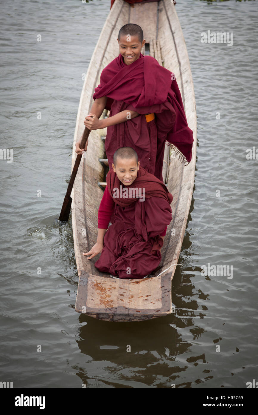 Novice Buddhist monks having fun on a small craft, at Maing Thauk (Myanmar). Young novices are also allowed to play - Stock Image