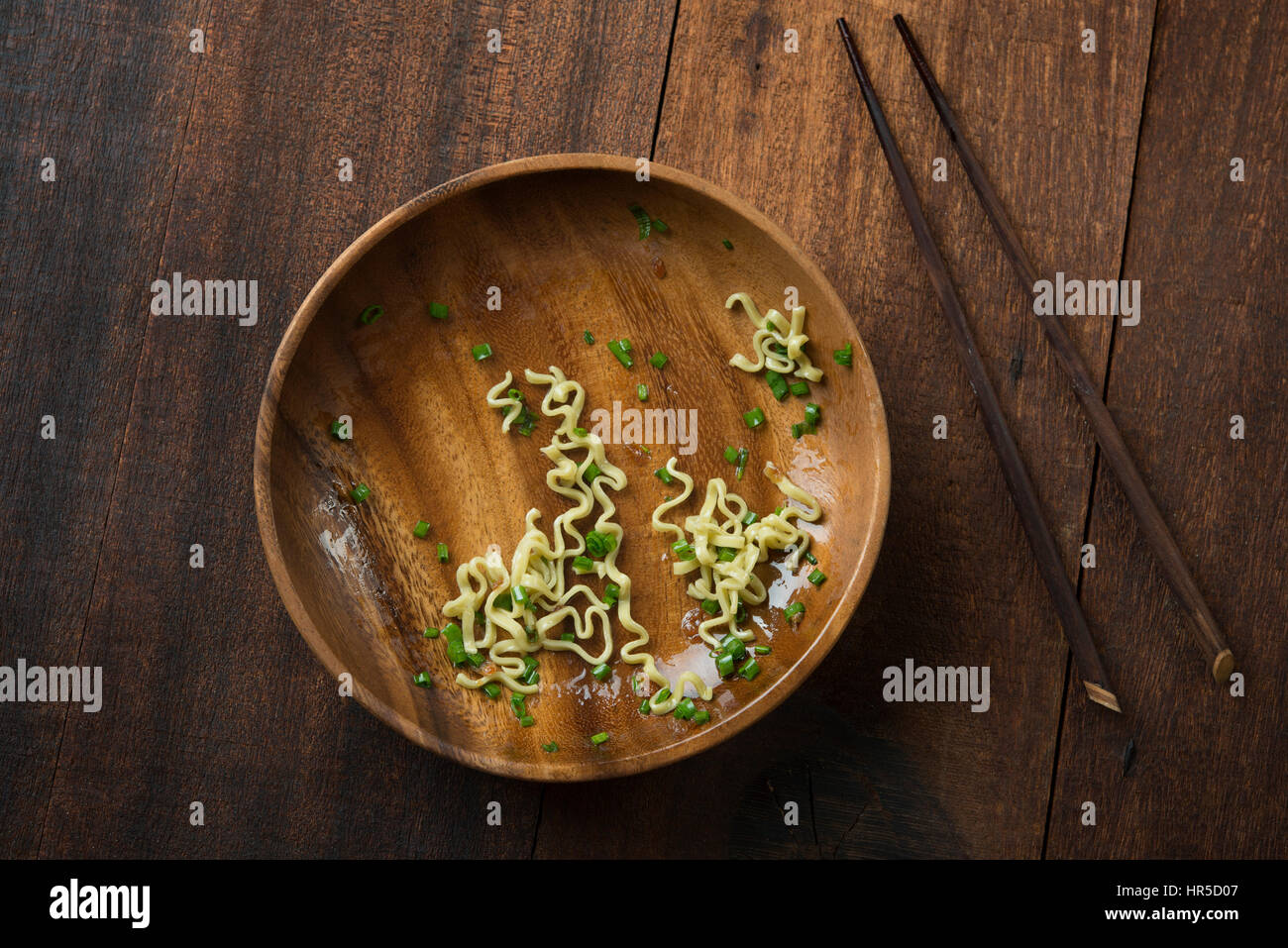 Top view leftover food Japanese ramen dried noodles with chopsticks on rustic wooden table. - Stock Image