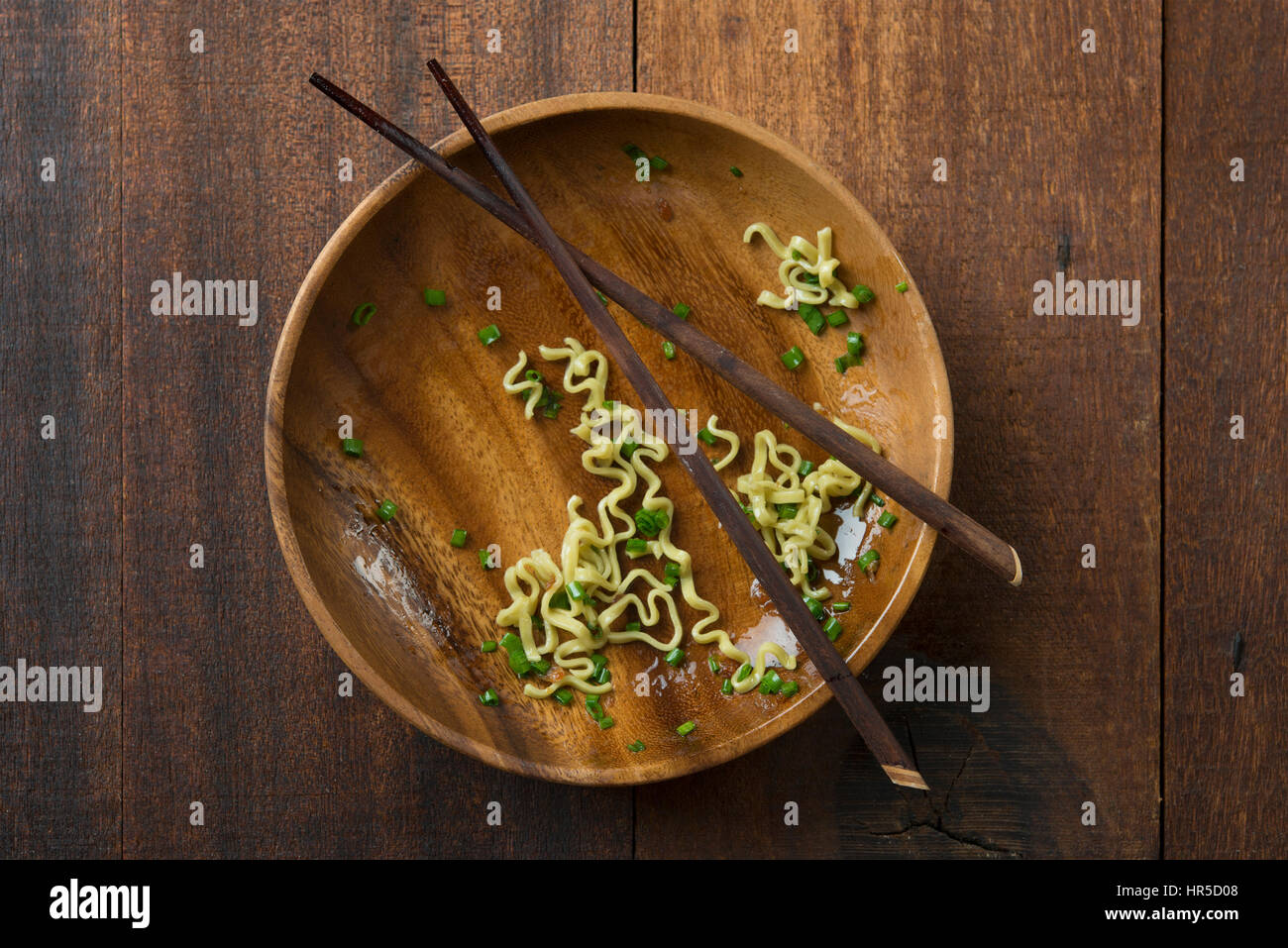 Top view leftover food dried noodles with chopsticks on rustic wooden table. - Stock Image