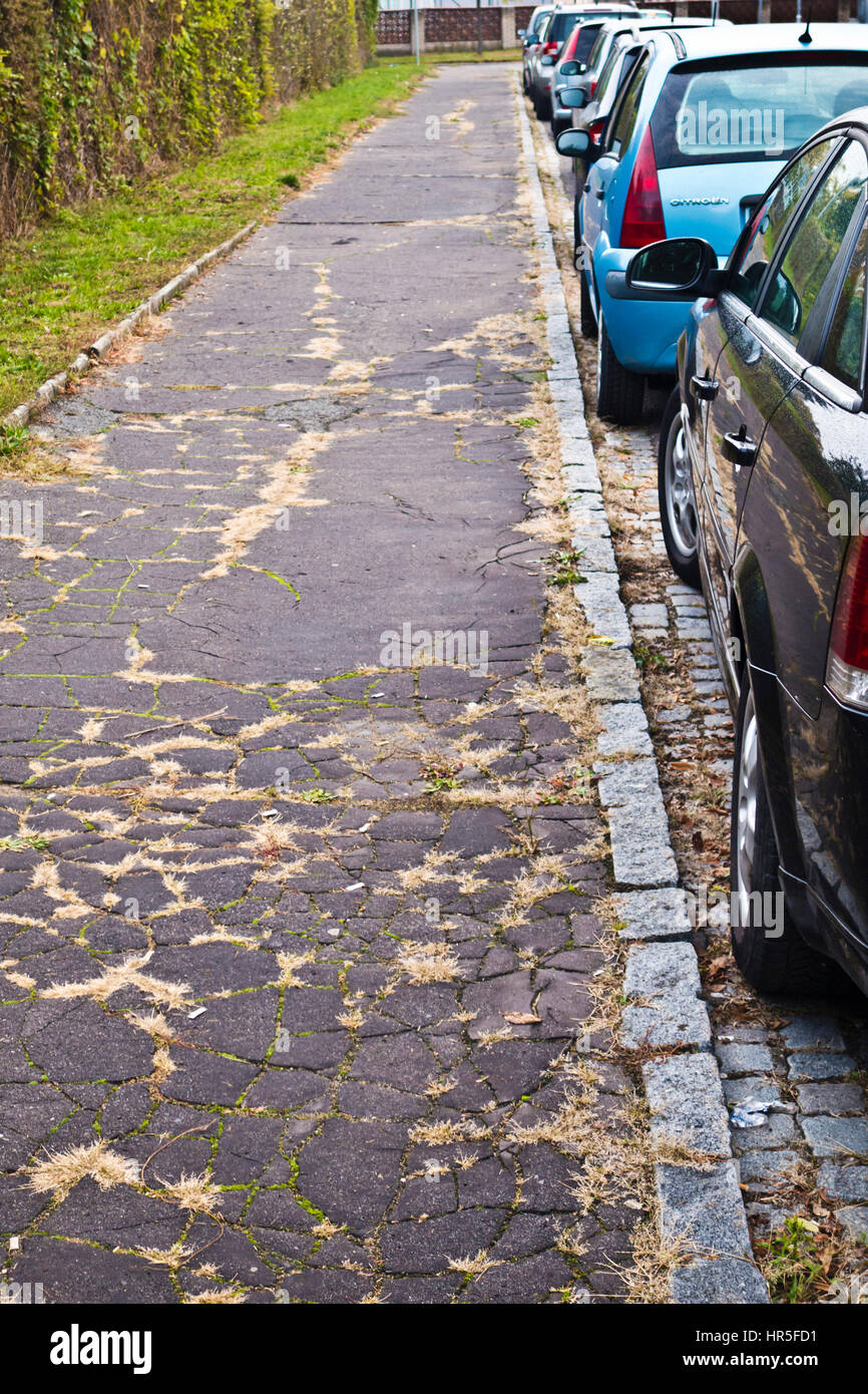 row of cars parked along a sidewalk in a city street - Stock Image