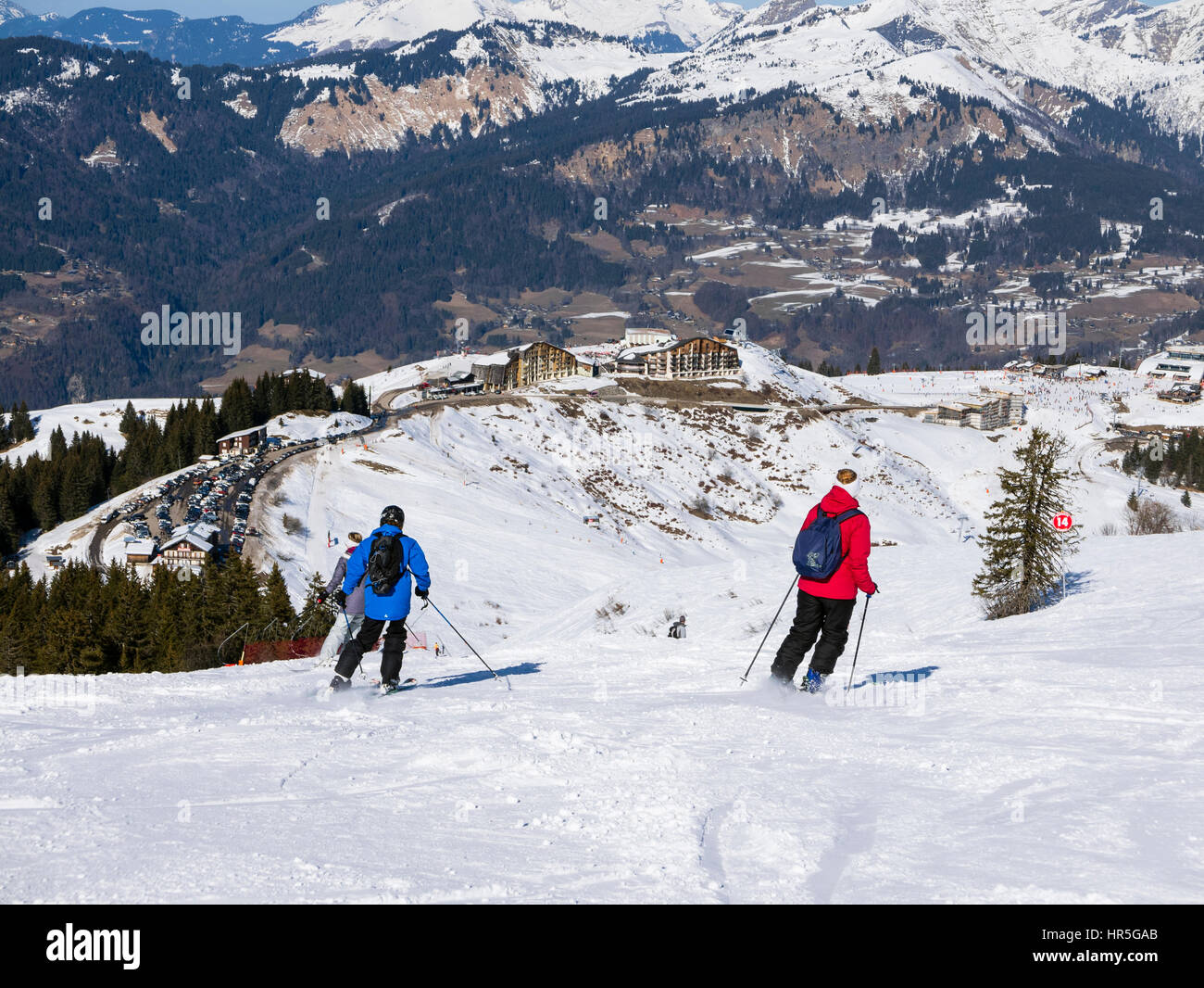 Skiers skiing on red run Marmotte in Grand Massif ski area of French Alps above Samoens, Haute Savoie, Rhone-Alpes, - Stock Image