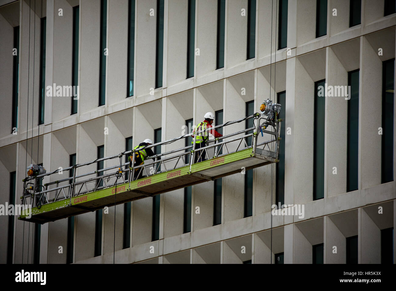 Wearing safety harnesses working high Window cleaners form a specialist access equipment cradle in Peter Square - Stock Image