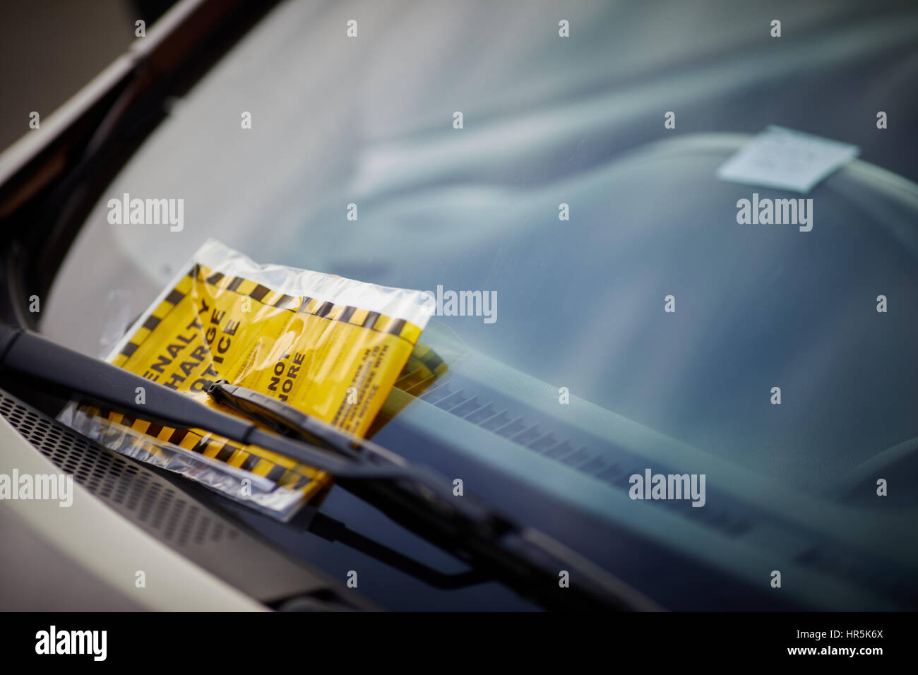 Manchester City Council official Penalty Charge Notice parking fine attached car windscreen plastic warning bag - Stock Image