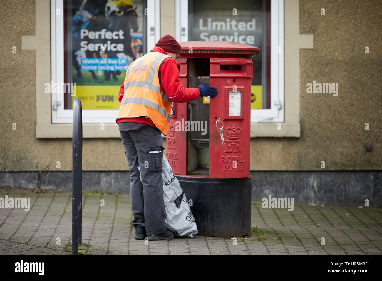 Postman in uniform emptying letters from a red Royal Mail postbox at Hare Hill Road, Littleborough Village, Rochdale, - Stock Image