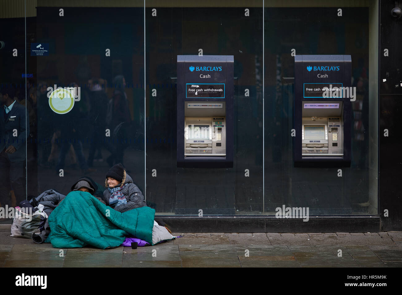 Barclays bank exterior Manchester Market Street homeless couple sit near ATM  Cash Machines    England,UK. - Stock Image