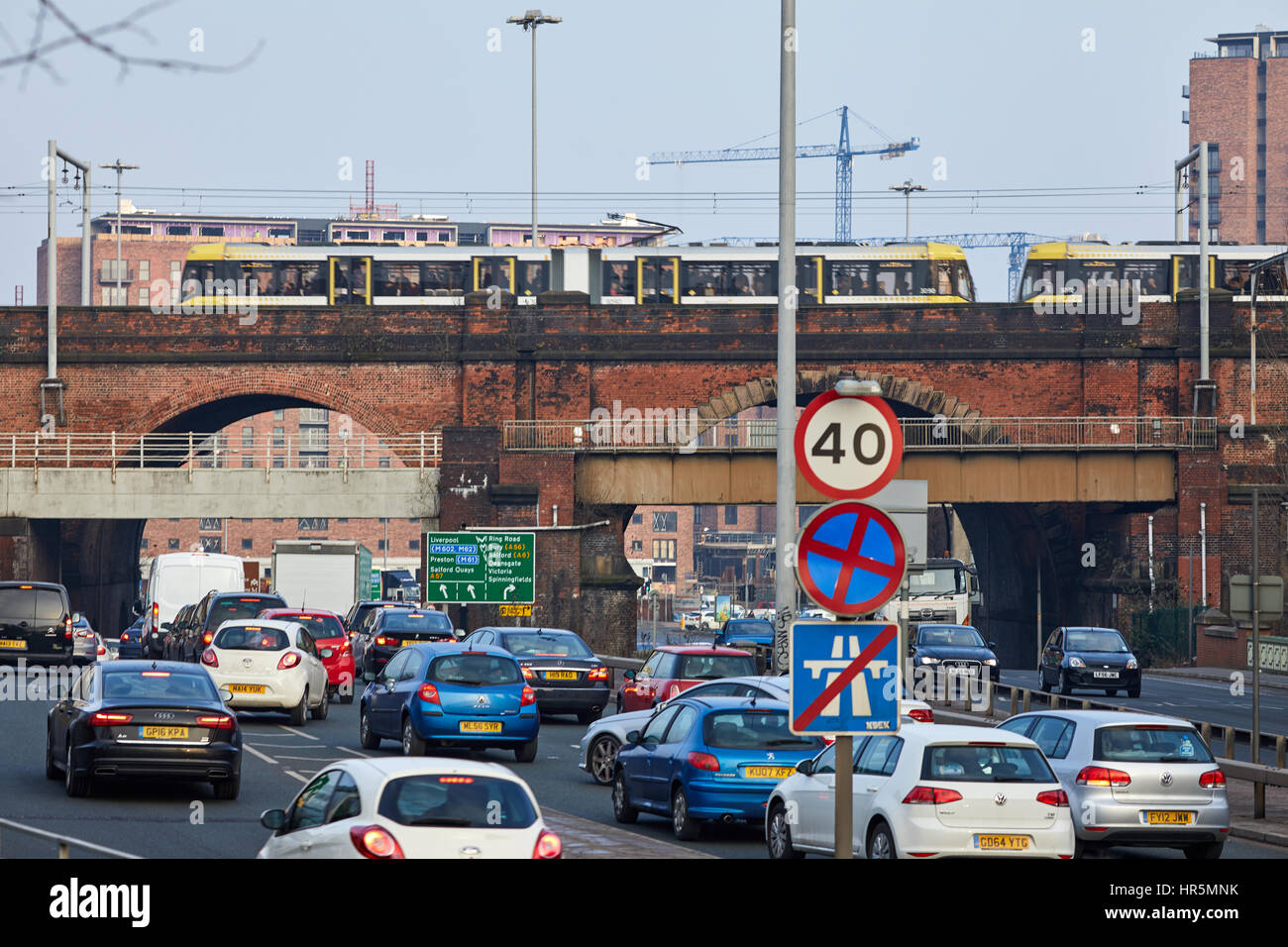 A yellow  Metrolink tram crossing a viaduct at  The Mancunian Way at  Castlefield Salford boundary Manchester England,UK - Stock Image