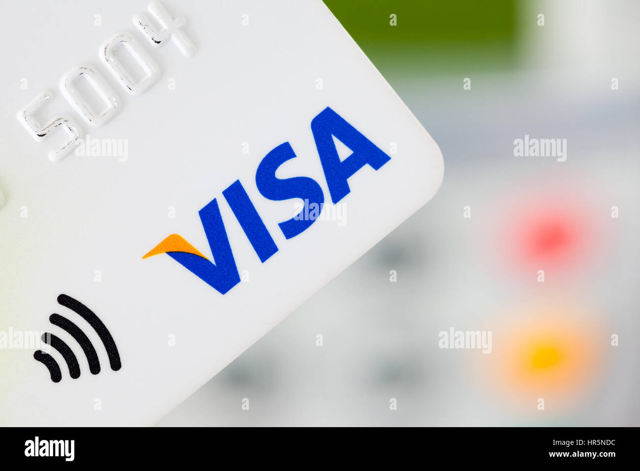 BATH, UK - JANUARY 20, 2014: Close-up of a contactless Visa credit card with a card machine in the background. The - Stock Image