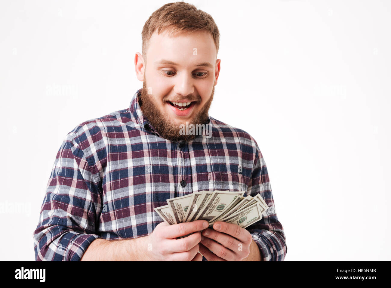 Bearded man in shirt considers money in studio. Isolated white background - Stock Image