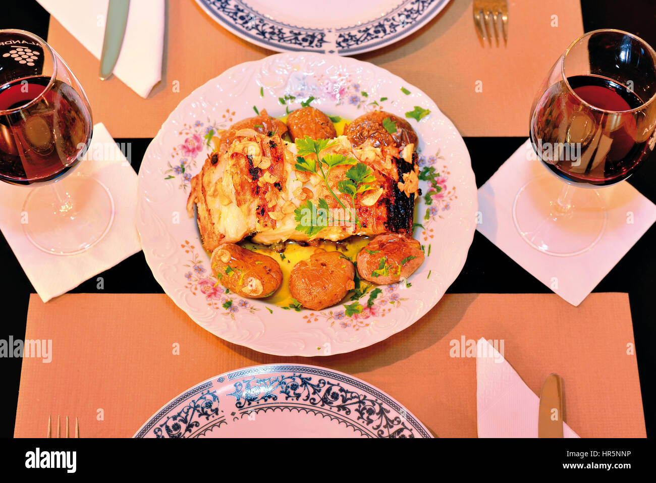 Grilled cod fish with potatoes on a prepared dinner table for two - Stock Image