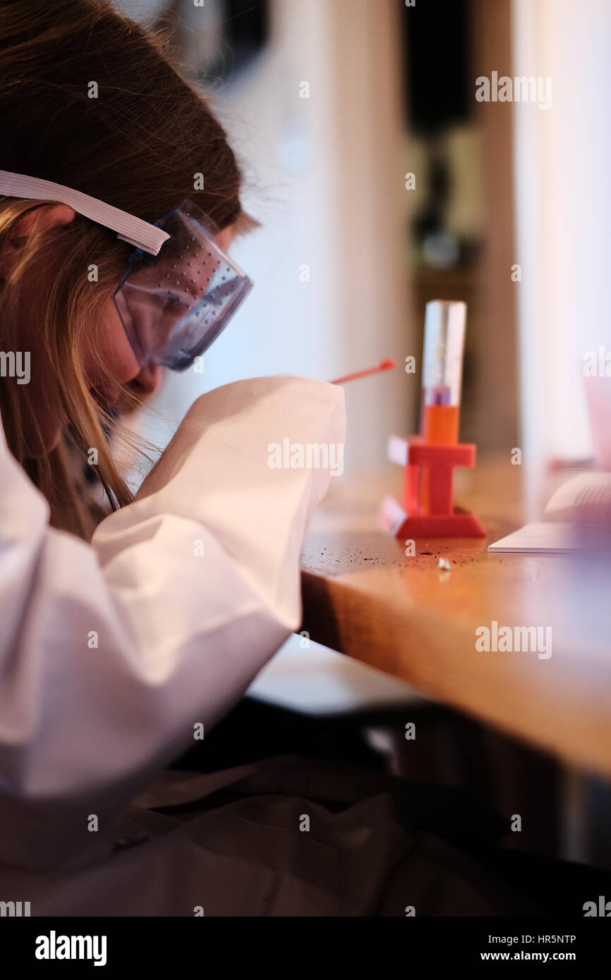 Young girl in white lab coat playing with chemistry science set - Stock Image