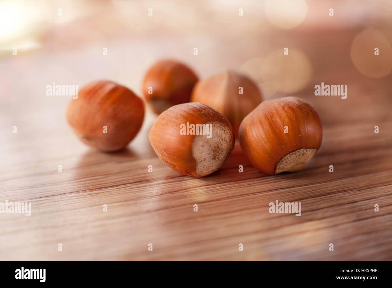 hazelnut close-up over the wooden table, soft shalow dof and bokeh, warm colors - Stock Image