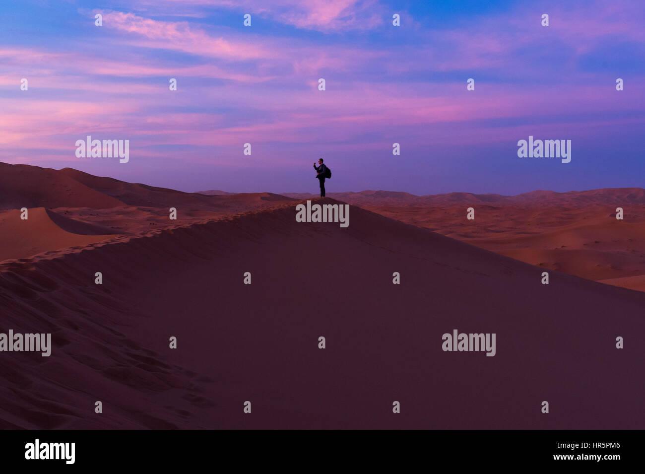 Tourist standing alone on one dune in Sahara Desert during Sunset - Stock Image