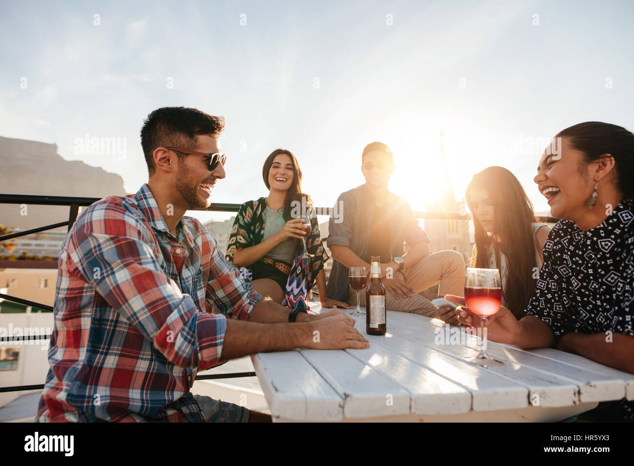 Multiracial group of friends having cocktail party on the rooftop. Young men and women sitting around table with - Stock Image
