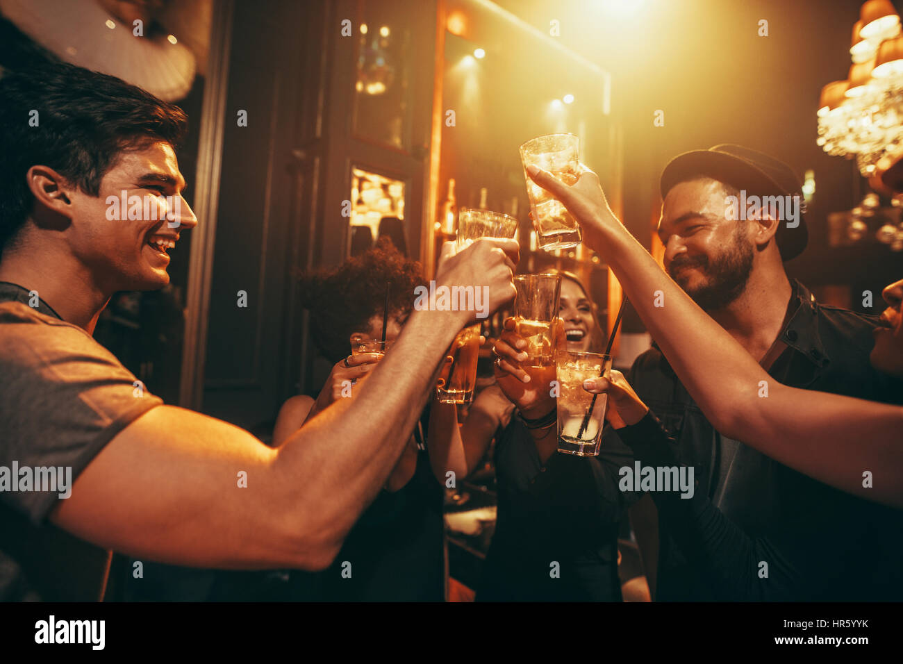 Young people celebrating and toasting drinks at nightclub. Friends having good time at club. - Stock Image