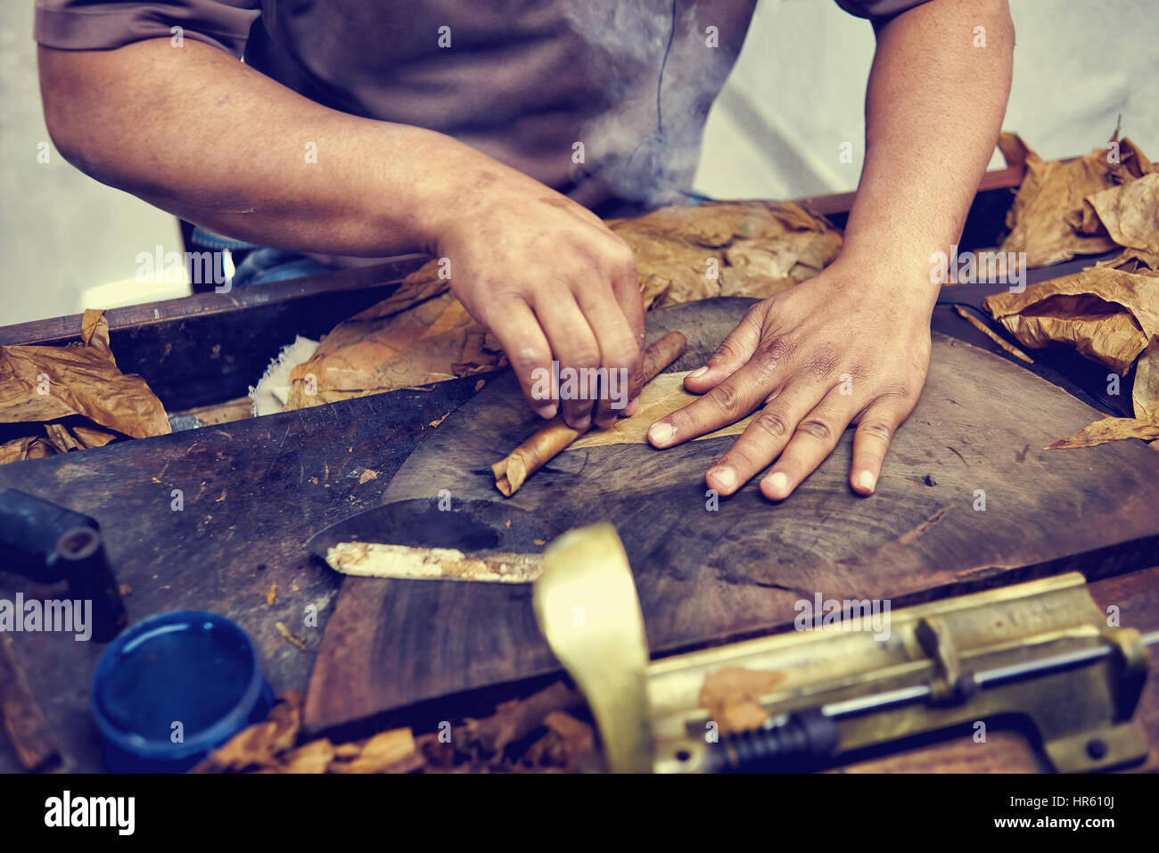 Closeup of hands making cigar from tobacco leaves. Traditional manufacture of cigars. Dominican Republic - Stock Image