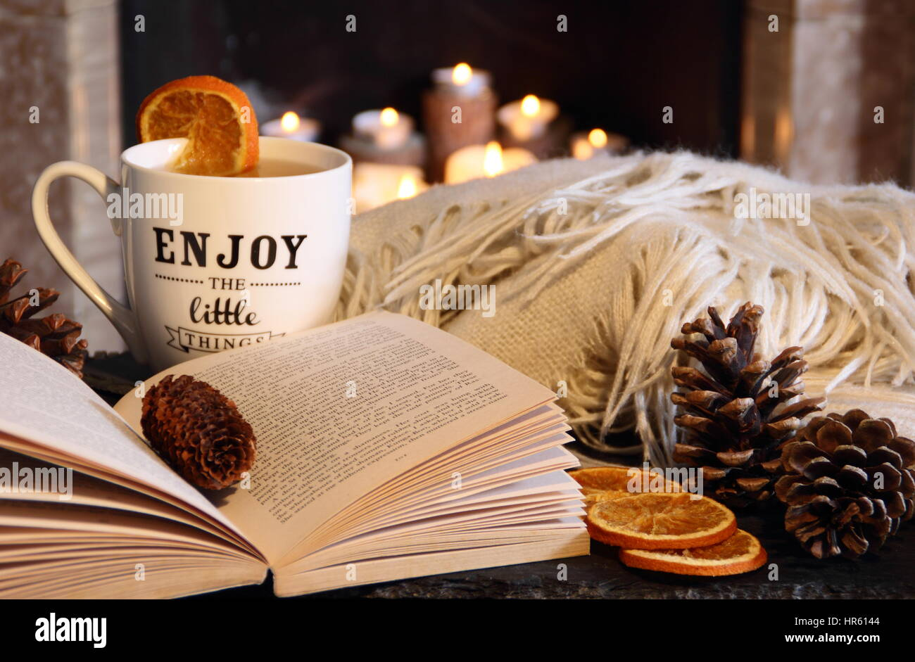 Reading a book by an open fireplace in a cosy hygge inspired English living room with a hot drink and blanket (throw) - Stock Image