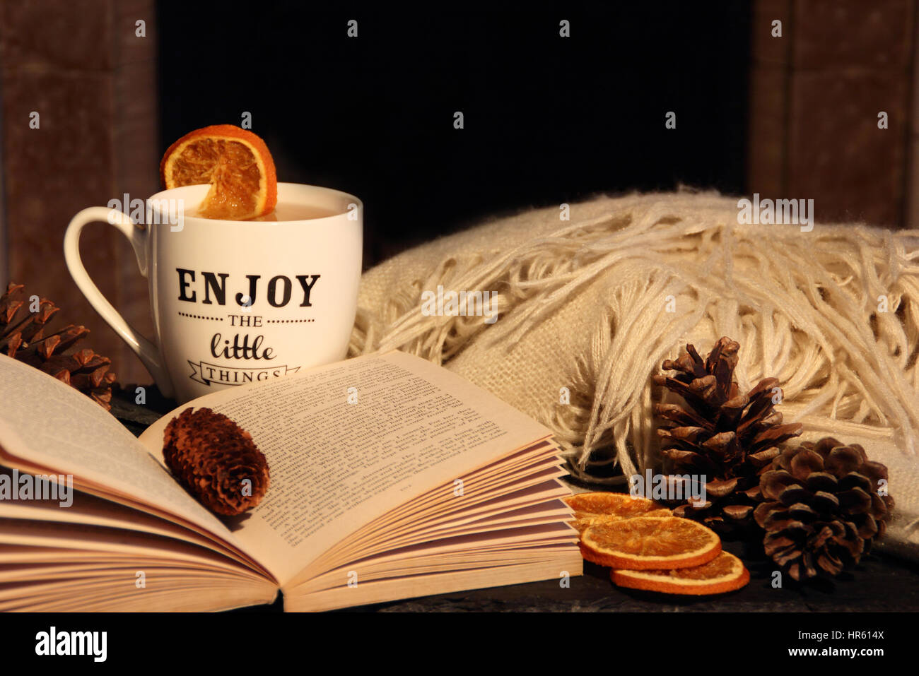 Reading a paperback book by a fireplace in a cosy hygge inspired English living room with a hot drink and blanket - Stock Image