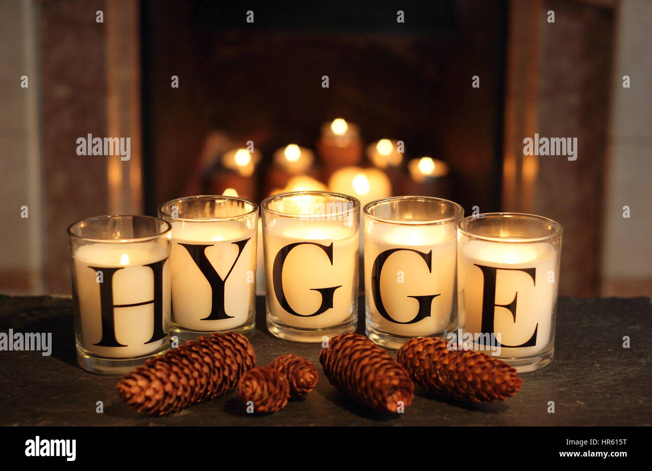 Fireside candles in an English home in winter depict 'hygge' - the Danish concept of embracing cosy contentment - Stock Image