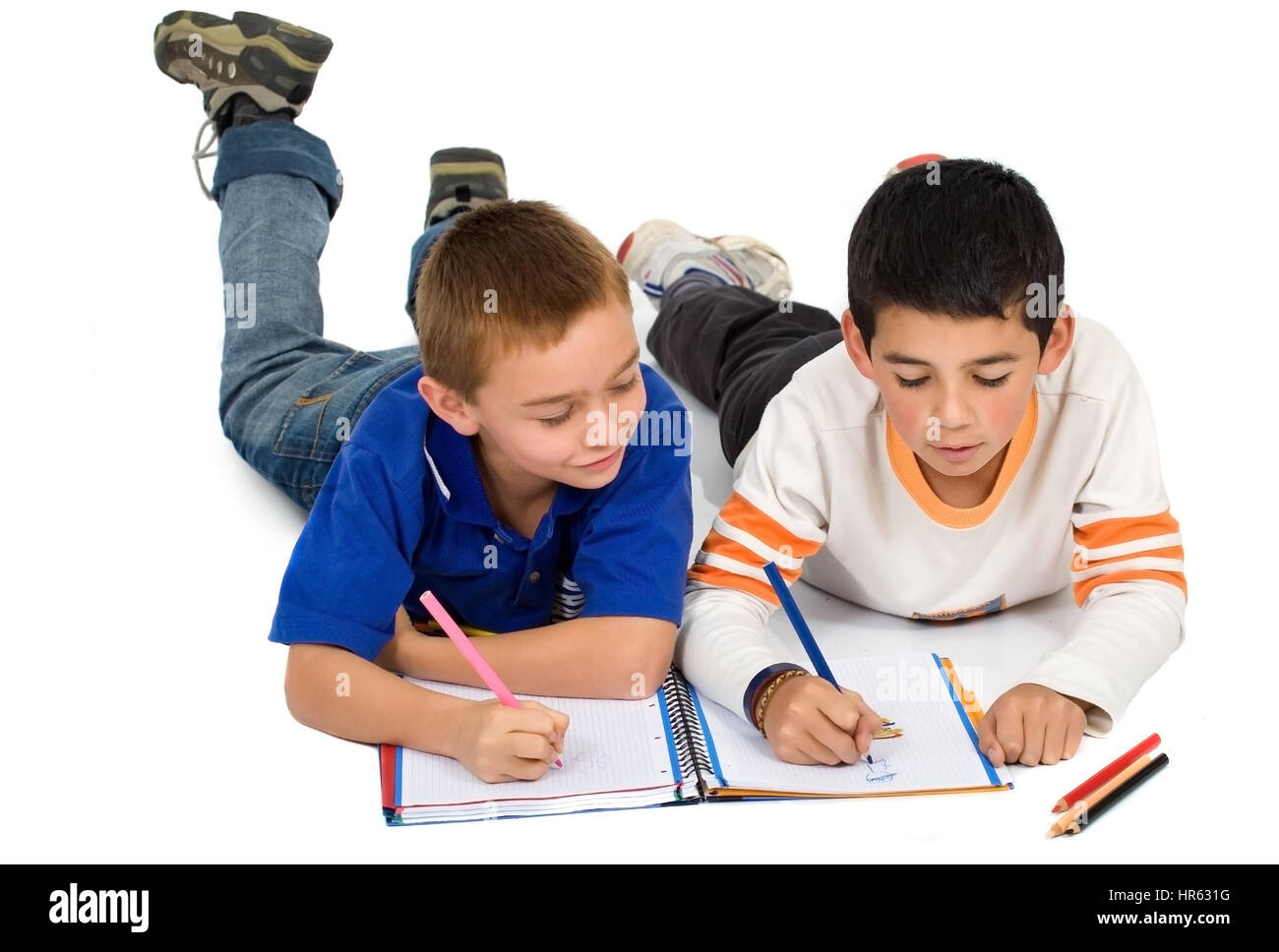 kids drawing on a notebook on the floor – isolated over a white background - Stock Image