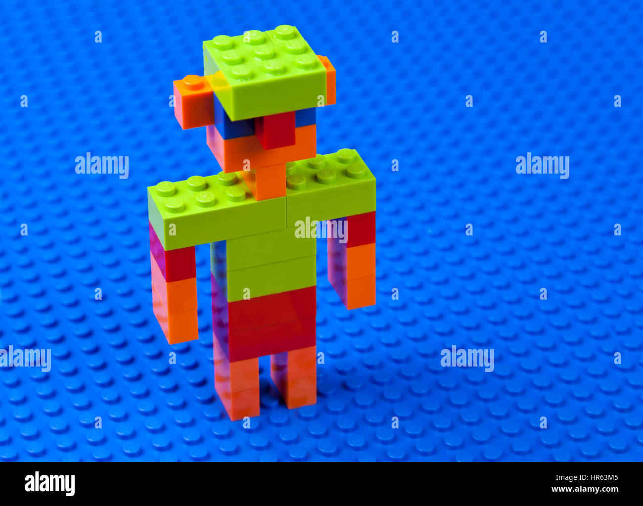 Man,  boy, male with jug-ears and a green cap built of Lego bricks on a blue Lego base plate -  dabbling or wading - Stock Image