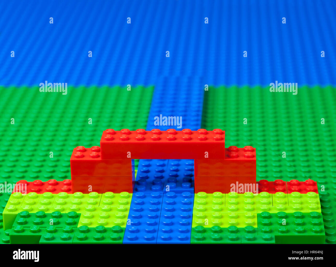 Lego landscape with bridge over river, stream, canal, etc. - green meadows or marshland and the blue sea. - Stock Image