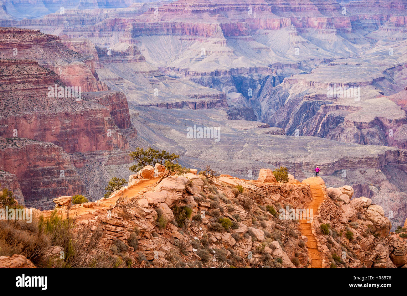 Looking don the kaibab trail a woman stands on an overlook, Grand Canyon's south rim, Grand Canyon National - Stock Image