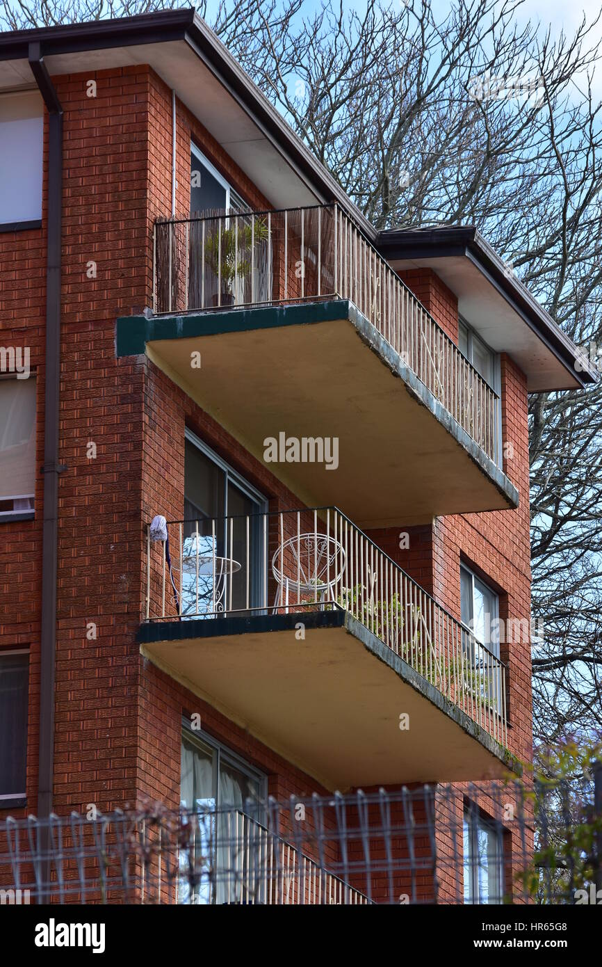 Red brick multi-story apartment building with balconies. - Stock Image