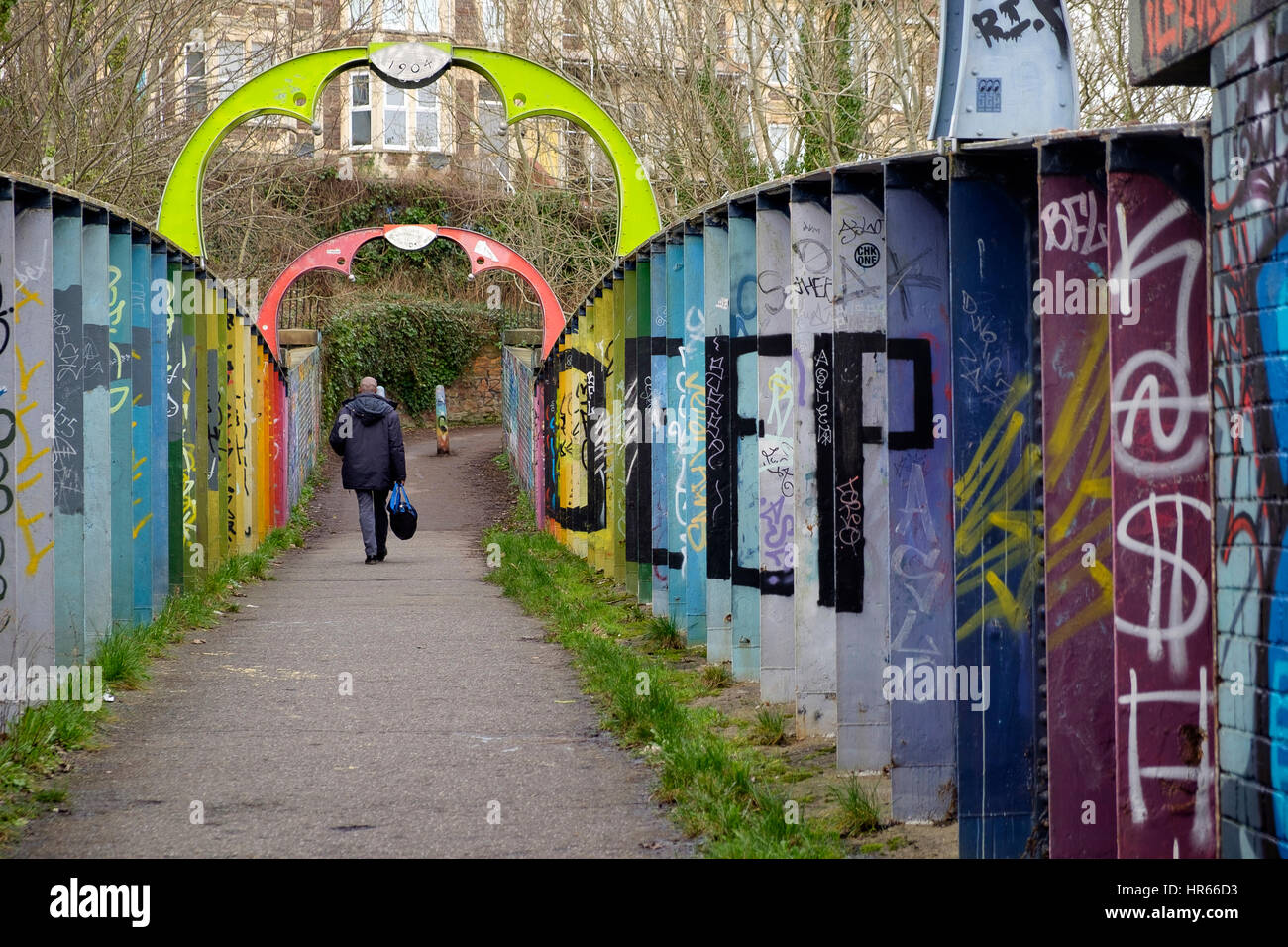 A man walks over a footbridge on a railway line in Montpelier, Bristol that is adorned with colourful streetart - Stock Image
