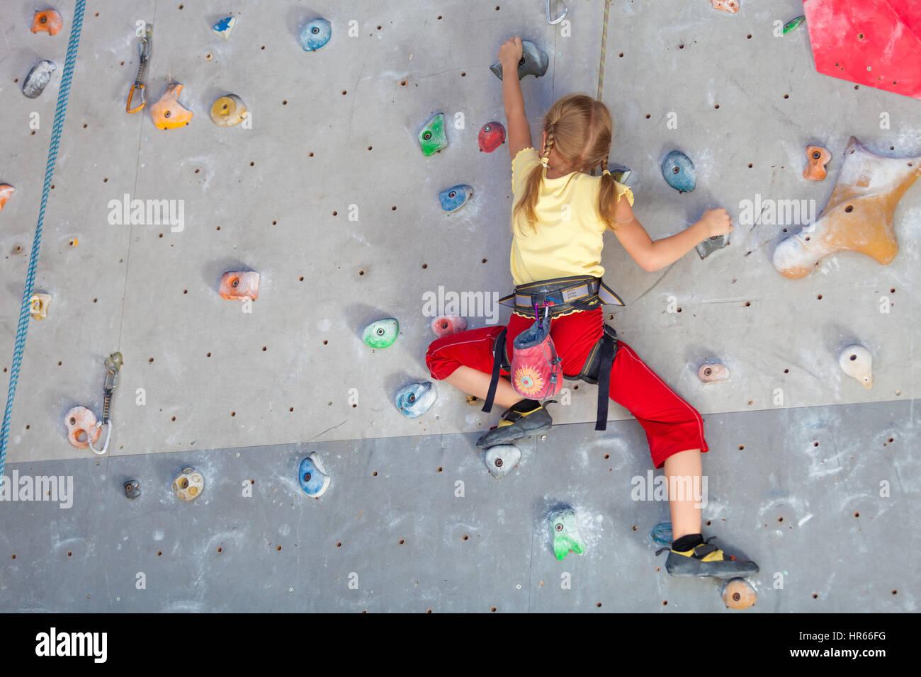little girl climbing a rock wall indoor - Stock Image