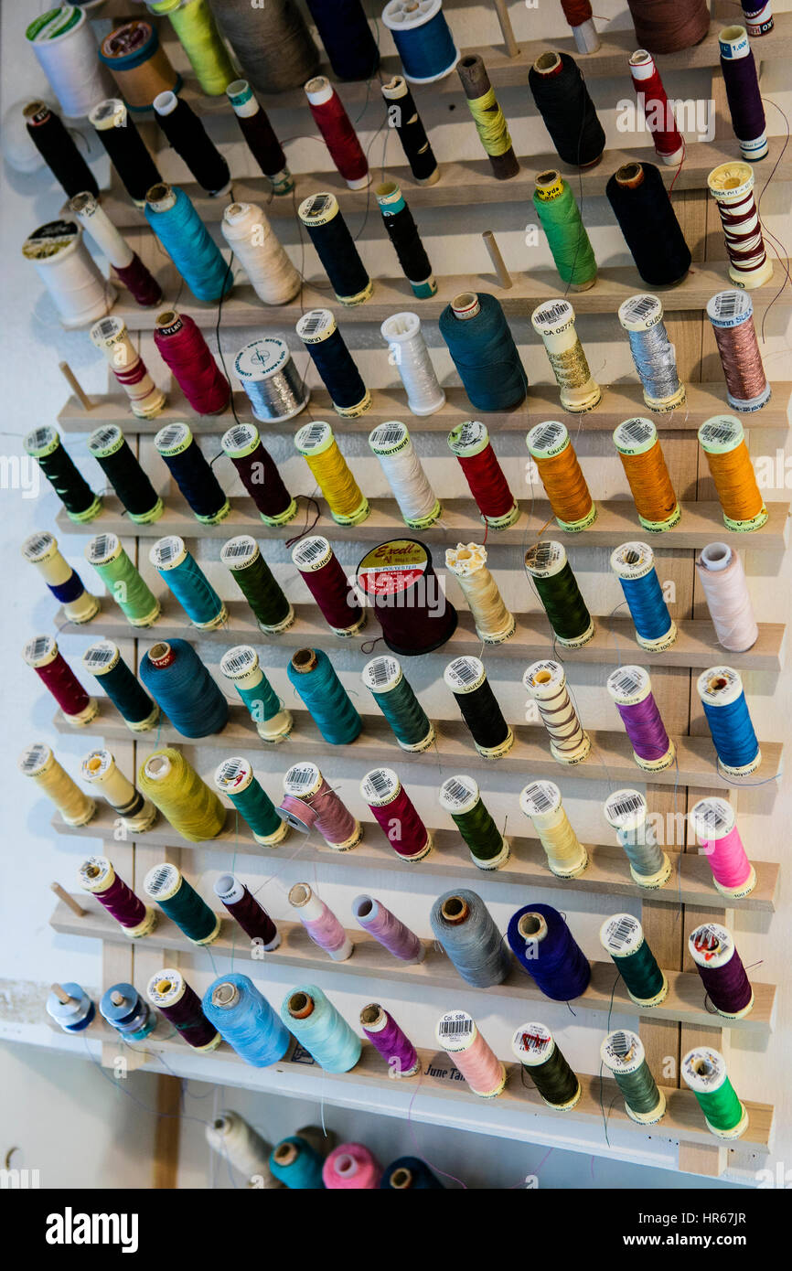Spools of cotton thread in dress alteration shop - Stock Image
