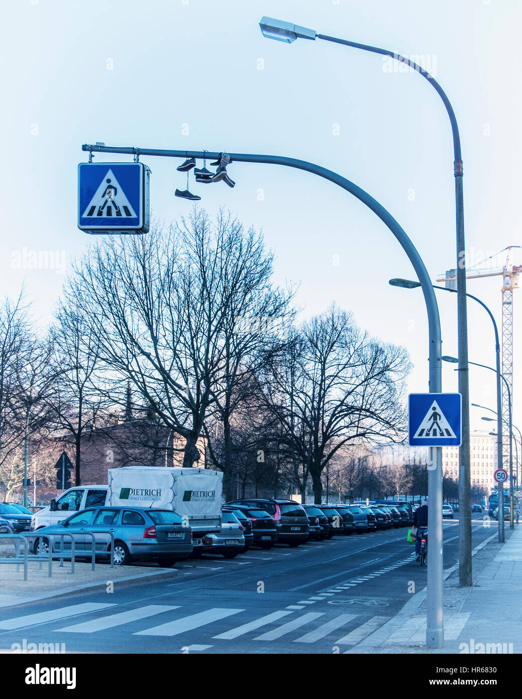 Berlin, Friedrichshain,Friedenstraße. Shoes,trainers suspended from a pedestrian crossing sign. concept, these - Stock Image