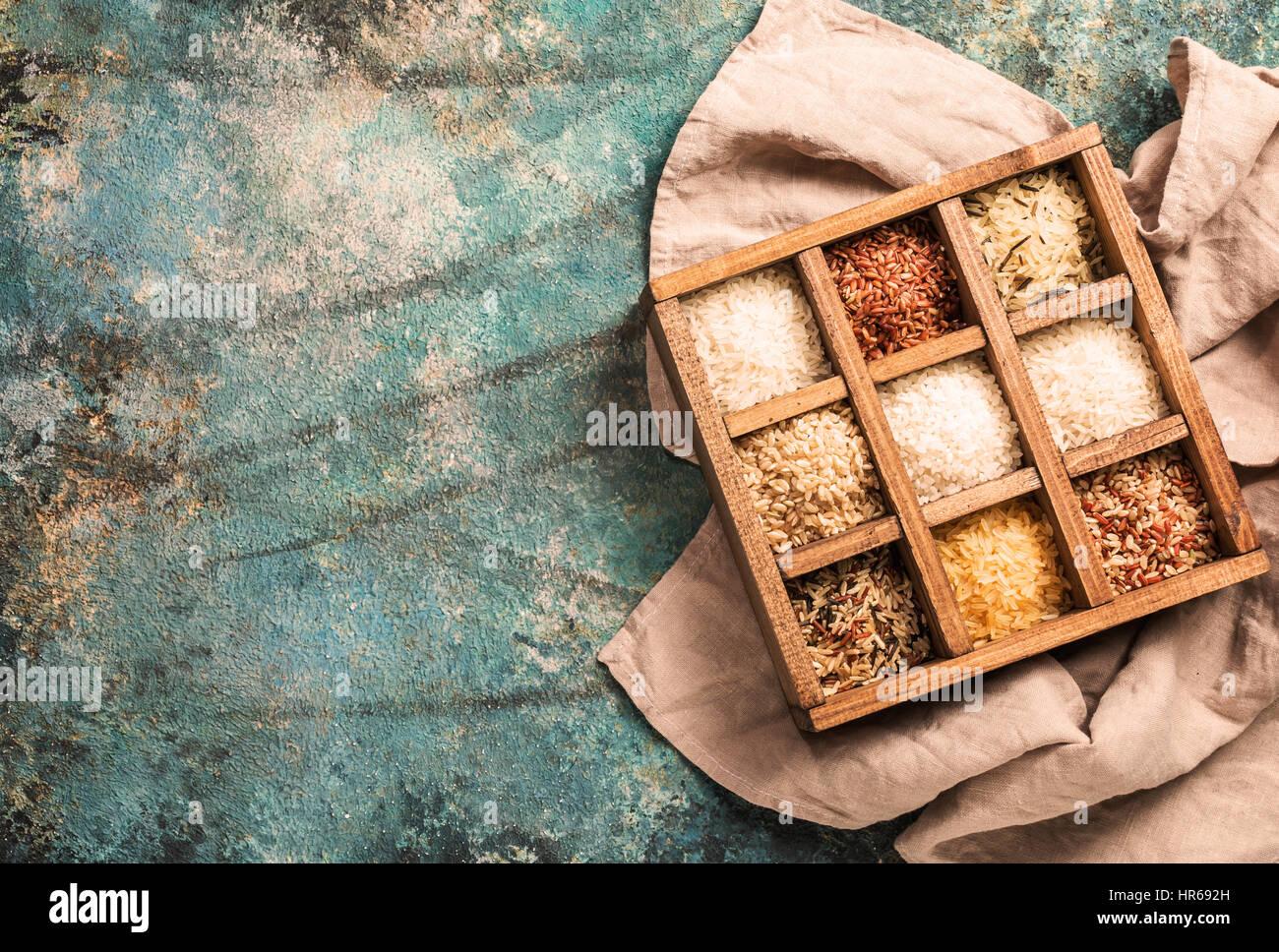 Varieties of rice in printers box, jasmine, wild, white, pearl, forbidden, jade, basmati and barley Top view - Stock Image