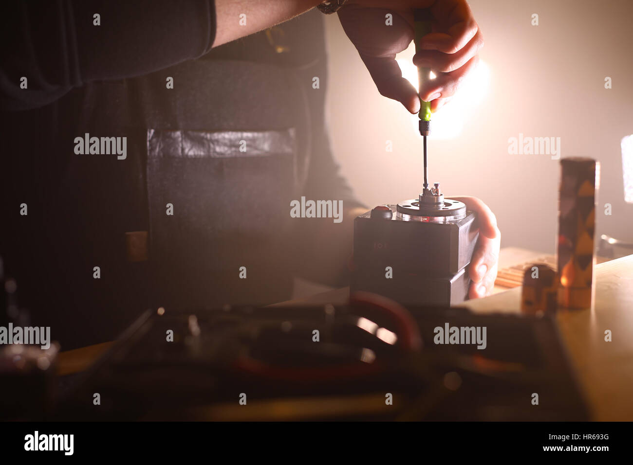 test burning the new dual kanthal micro coils on the atomizers deck base of electronic cigarette for vaping, close - Stock Image