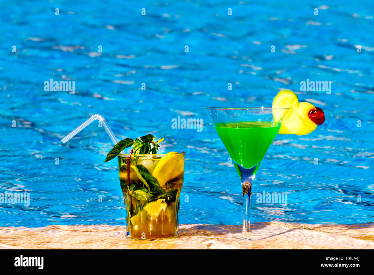 Beautiful multi-colored cocktails on swimming pool background, girls and palm trees - Stock Image