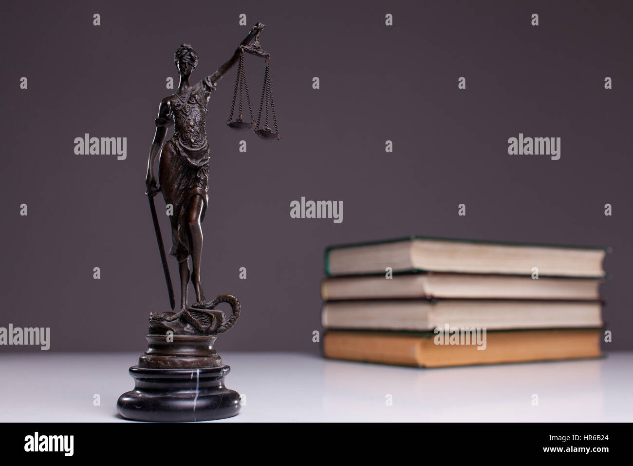 The goddess of justice on a white table against the background of the books. - Stock Image
