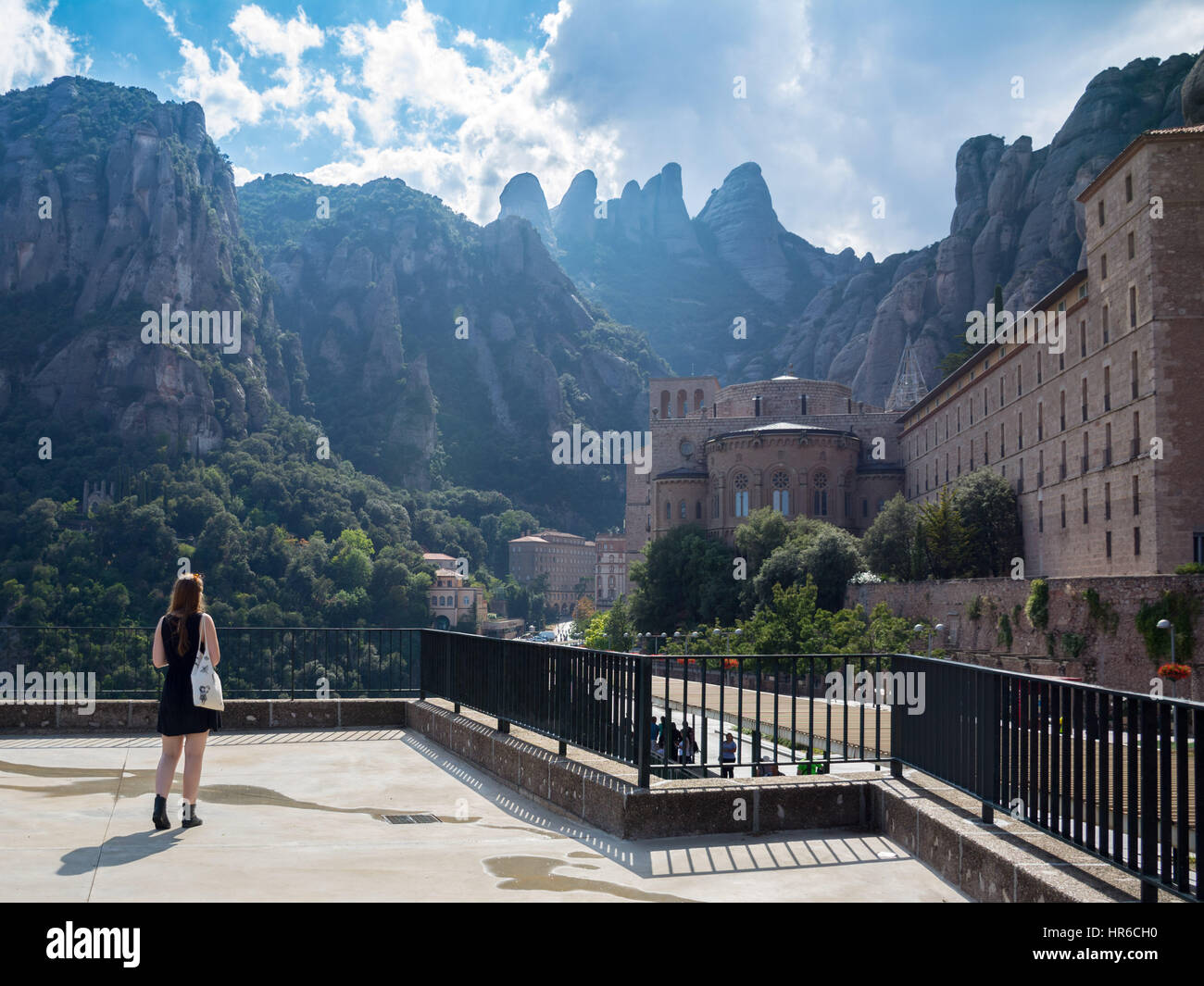 Young woman traveler enjoying the view of mountains on the background. Montserrat. Spain. Europe. - Stock Image