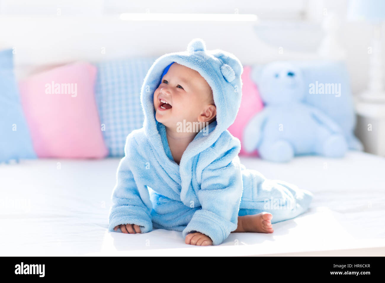 Cute happy laughing baby boy in soft bathrobe after bath playing on ...