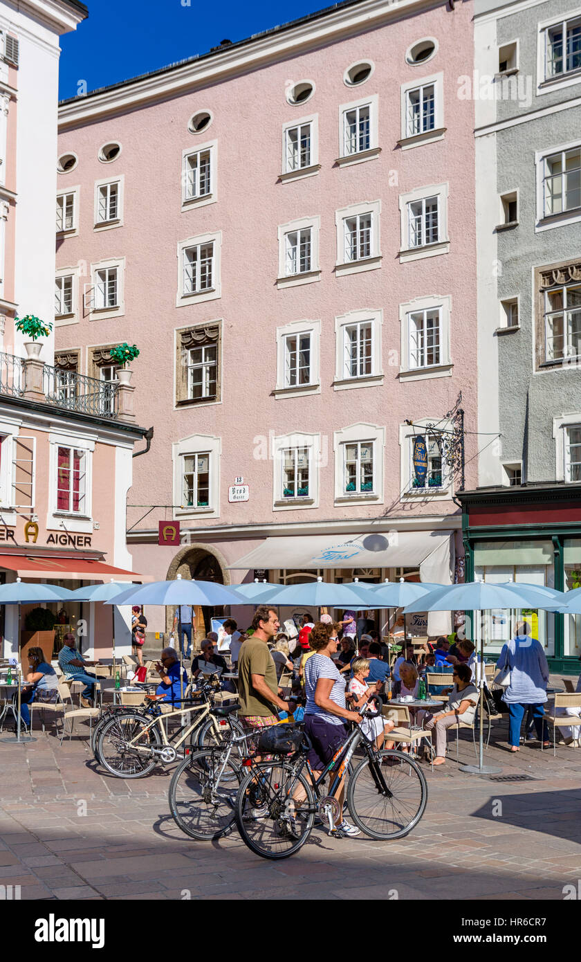 Cyclists in front of a cafe in the Alter Market, Salzburg, Austria - Stock Image